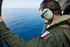 Handout picture provided by the French Army shows a French military transport crew member inspecting the Indian Ocean during a search mission along the coast near Saint-Andre on the French island of Reunion